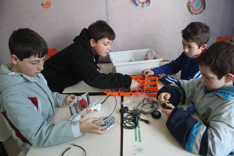 João Vitor, 10 anos (superior à esquerda) e Luis Miguel, 11 anos (inferior à esquerda) programam coluna vertebral de uma chita, com lego.