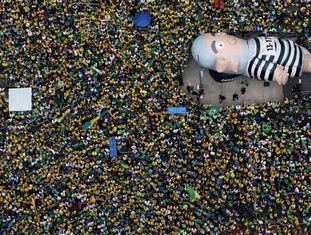 Manifestantes levantam o boneco que remete ao ex-presidente Lula, na avenida Paulista, no domingo (13).