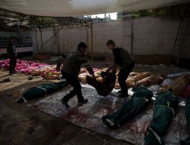 Dois homens transportam os corpos de várias vítimas do ataque a um mercado de Duma, nesta sexta-feira.