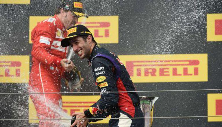 Ricciardo festeja sua vitória na Hungria, com Alonso ao fundo.