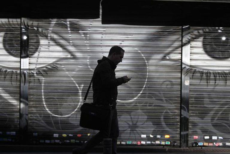 Homem caminha usando celular em uma rua de Madri.
