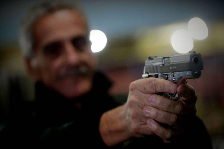 Homem segura pistola da Taurus em São Paulo.