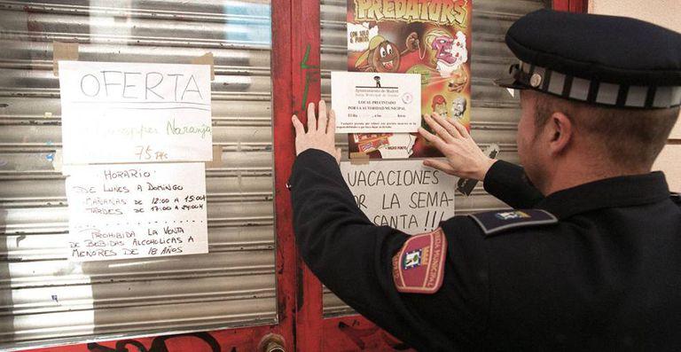 Policial municipal coloca um cartaz numa loja fechada por vender bebida alcoólica a menores em Madri.