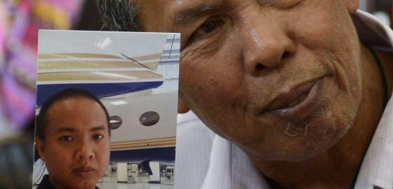 Homem mostra a foto de seu filho, Mohd Khairul Amri Selamat, um dos passageiros do voo MH370.
