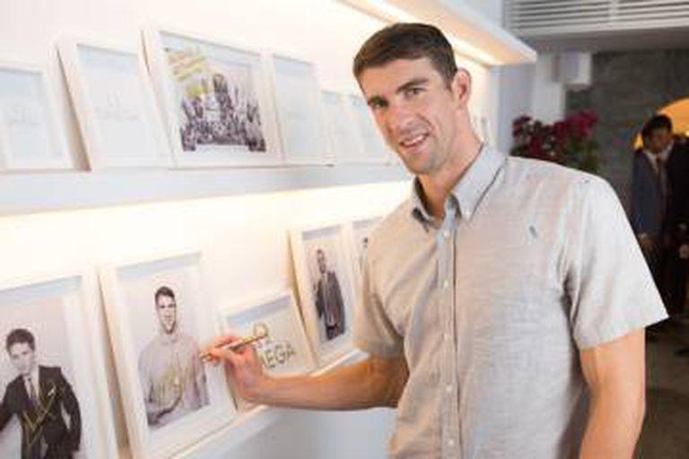 Phelps autografa sua foto no pequeno 'hall of fame' da Omega House na Vila Olímpica do Rio 2016.