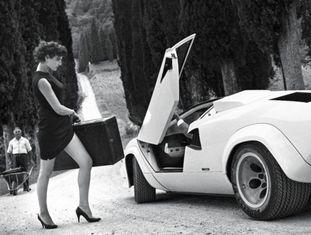 A modelo Antonia Dell'Atte, com um vestido justo e sapatos de salto alto, se encaminha decidida para um carro esportivo