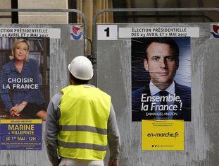 Operário observa cartazes dos candidatos do segundo turno na França.