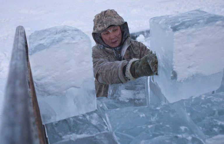 Ruslan, 35 anos, carrega blocos de gelo em um caminhão na periferia de Yakutsk, no vale de Oymyakon.