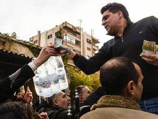 Um homem vende garrafas de água mineral num bairro de Damasco.