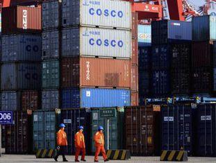 Três trabalhadores diante de vários contêineres no porto de Qingdao, leste da China.
