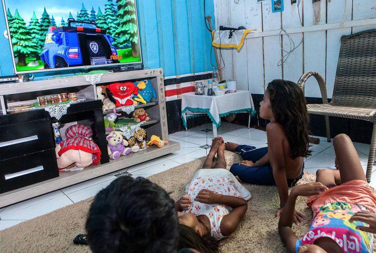 Em foto de 24 de março de 2017, Alice (sentada) assiste a desenhos na TV, hoje principal lazer das crianças indígenas, proibidas de se aproximar do rio.