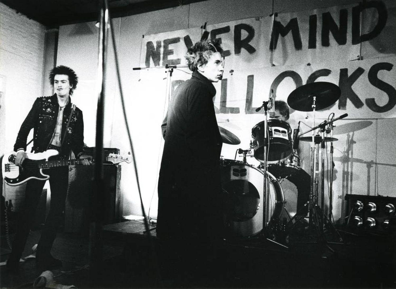 Sid Vicious, Johnny Rotten e Paul Cook, membros do Sex Pistols, em um show em 1977. Ao fundo, o título de seu primeiro e único disco, 'Never Mind the Bollocks'.