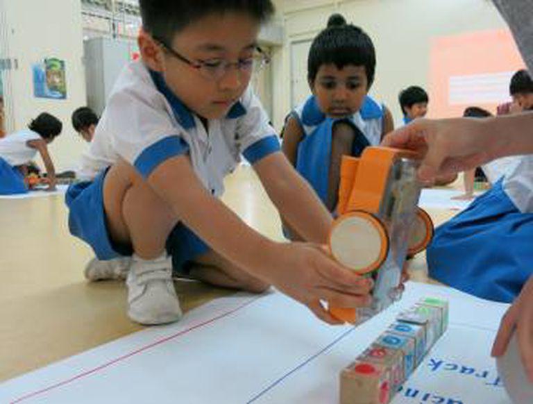 Criança da pré-escola brinca com o Kibo, um brinquedo robotizado.