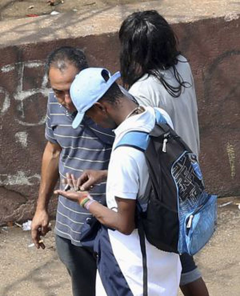 Usuários contam pedras de crack na rua.