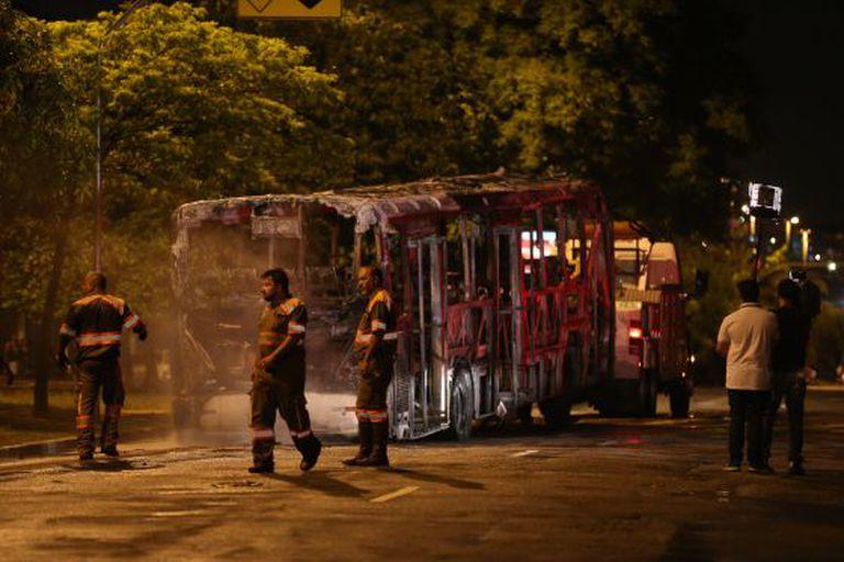 Técnicos retiram ônibus incendiado na zona norte de São Paulo.