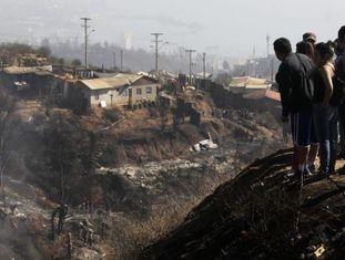 Um grupo de pessoas observa a área arrasada pelo fogo.
