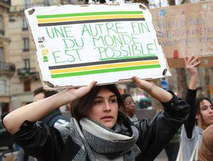"""Jovem segura placa dizendo """"um outro fim do mundo é possível"""" em protesto da Juventude pelo Clima na Antuérpia, Bélgica."""