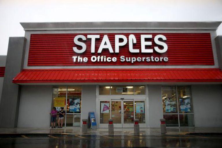 Em Miami, duas mulheres se protegem da chuva numa loja da Staples, rede que acaba de anunciar o fechamento de 12% dos seus estabelecimentos.
