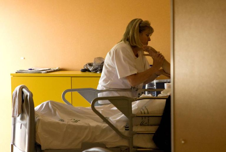 Uma enfermeira atende a um paciente na unidade de cuidados paliativos.