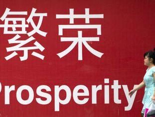 Mulher passa em frente a cartaz em Pequim.