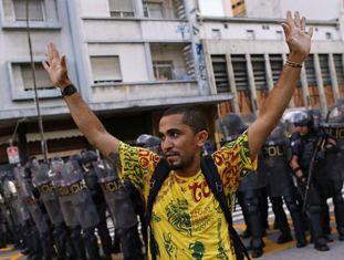 Manifestante diante de um cordão policial em São Paulo.