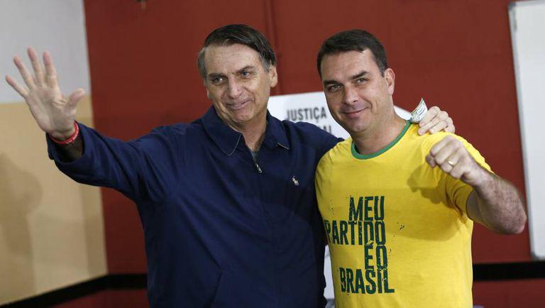 Bolsonaro e Flávio, no primeiro turno da eleição presidencial em 2018.
