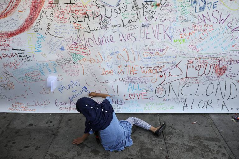 Uma criança escreve no muro junto à mesquita.