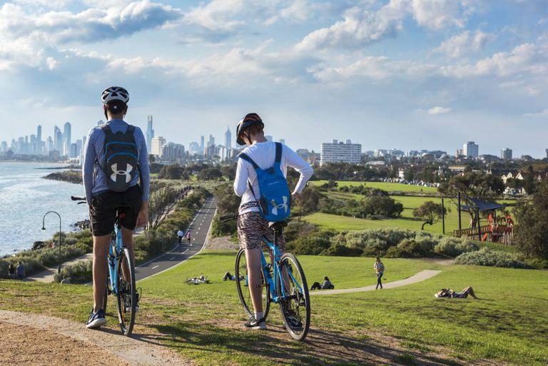 Dois ciclistas em Point Ormond, com o skyline de Melbourne ao fundo