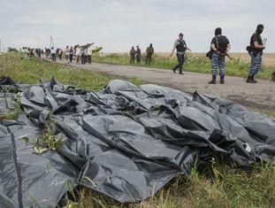 Rebeldes pró-russos ao lado dos corpos das vítimas do MH17, em julho.