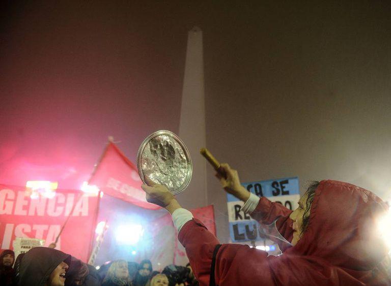Uma mulher bate panela durante protesto contra aumentos de preços em 14 de julho, em Buenos Aires.