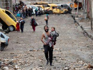 Homem foge com a filha de um lugar controlado pelo Estado Islâmico em Mossul, no sábado.