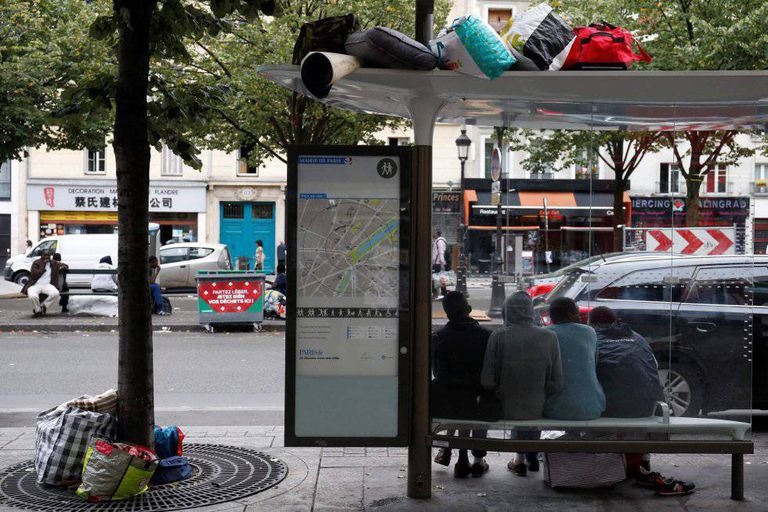 Migrantes esperam debaixo da parada do ônibus durante a evacuação do acampamento improvisado em Paris