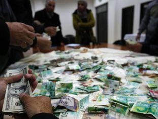 Palestinos contam o dinheiro arrecadado para reconstruir as casas de familiares de terroristas.