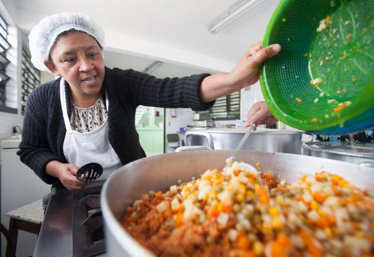 Funcionária cozinha a merenda em uma escola de SP.