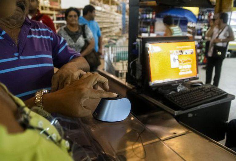 Clientes se identificam no sistema de compras biométrico em Maracaibo.