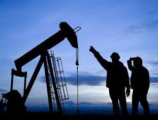 Dois trabalhadores observam um poço de extração de petróleo