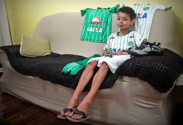 Em casa, o garoto exibe as chuteiras e as camisas da Chape.