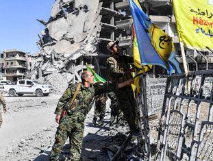 Membros das Forças Sírias Democráticas colocam sua bandeira na praça A o-Naim em Raqa nesta terça-feira.