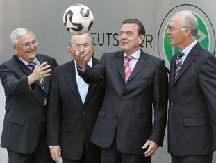 Gerhard Schröder brinca com uma bola de futebol diante de Theo Zwanziger (e), Joseph Blatter (2e) e Franz Beckenbauer (d).