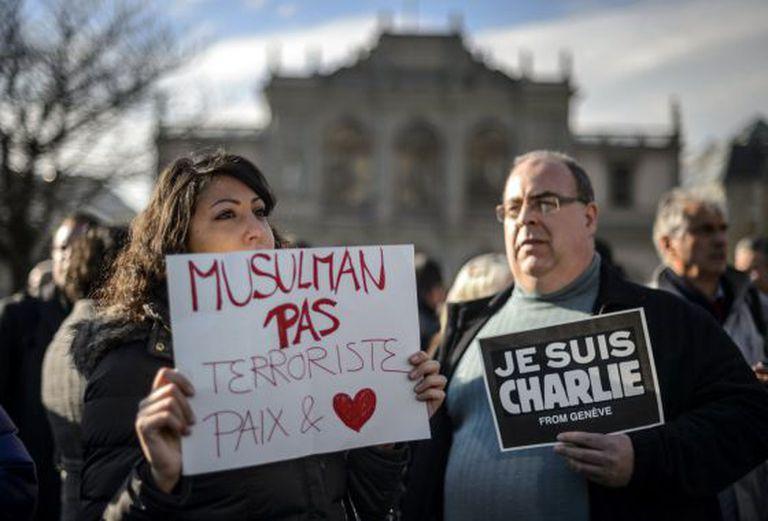 """Em Geneva, mulher carrega cartaz: """"muçulmanos não são terroristas""""."""