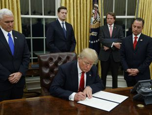O presidente Donald Trump, no centro, assinando sua primeira ordem executiva, em 20 de janeiro.