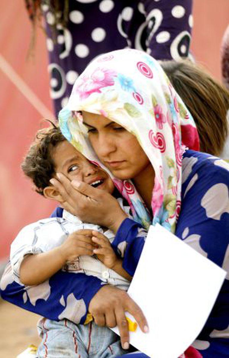 Uma refugiada síria consola seu filho na fronteira com a Turquia.