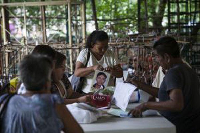 Membros do grupo reúnem informação sobre desaparecidos durante uma reunião.