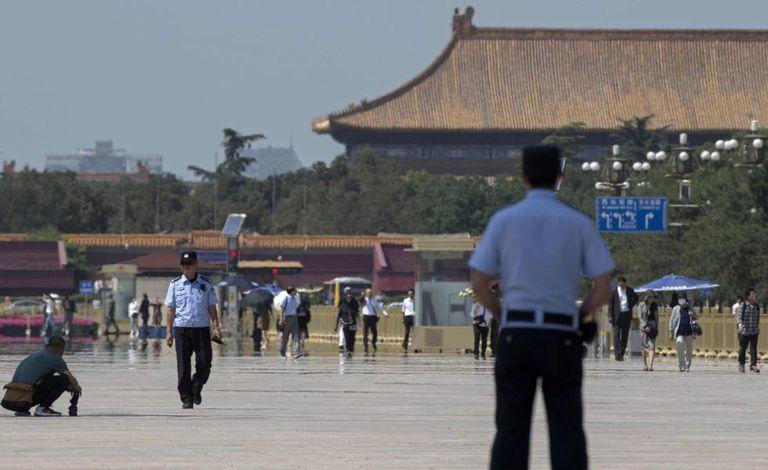 Agentes da polícia vigiam a praça Tiananmen, em Pequim, em 3 de junho