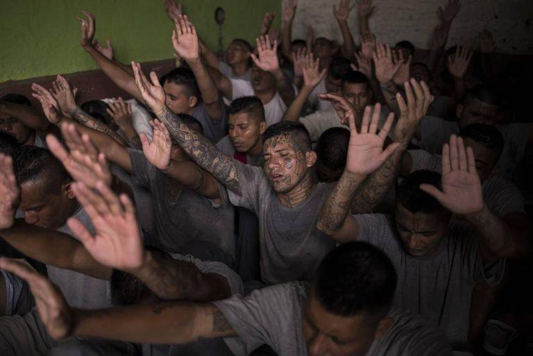 Antigos membros de gangues, presos na cadeia de Gotera, levantam as mãos durante o culto religioso