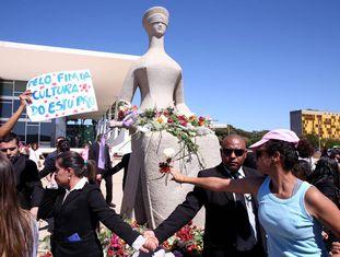 Mulheres protestam depositando flores na estátua da Justiça, em Brasília