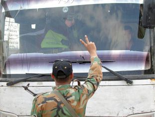 Soldados sírios fazem o símbolo da vitória em frente a um ônibus que evacua rebeldes em Duma, nos arredores de Damasco.