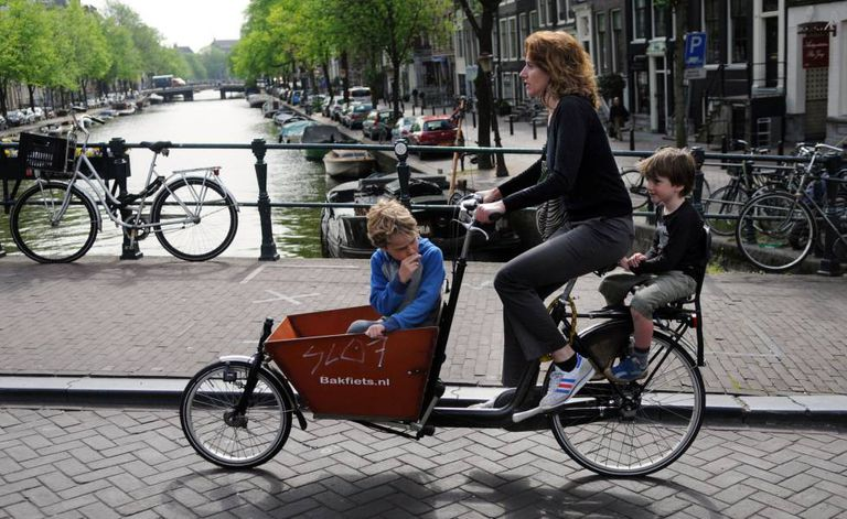Mãe com os filhos atravessando de bicicleta um dos canais de Amsterdã.