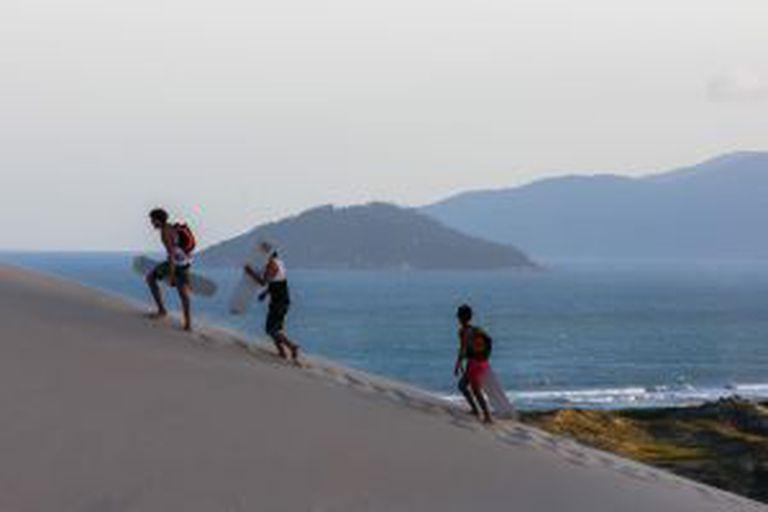 Praticantes de 'sandboard' na praia de Joaquina, em Santa Catarina (Brasil).
