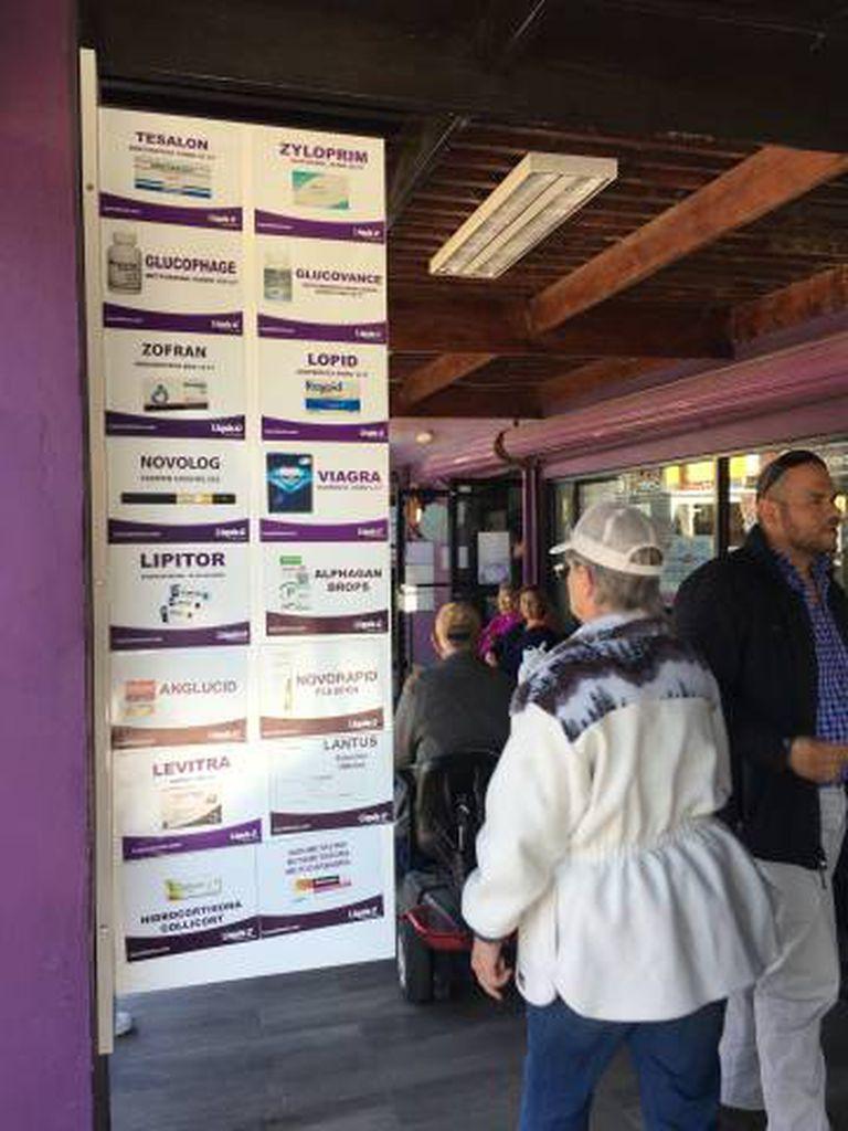 Turistas ao lado de anúncios de medicamentos em uma farmácia em Los Algodones, Baixa Califórnia